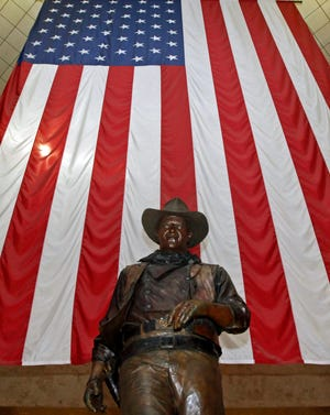 A bronze statue of late actor John Wayne stands before a four-story high United States flag at John Wayne Orange County Airport in Santa Ana, Calif., in 2011.