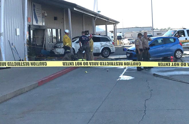 Deputies and firefighters stand outside the Red Bluff Walmart distribution center after a man reportedly opened fire there and rammed his vehicle into the building.