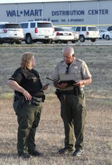 Lt. Yvette Borden and Assistant Sheriff Phil Johnston of the Tehama County Sheriff's Office talk between themselves before holding a press conference Saturday, June 27, 2020, outside the Red Bluff Walmart Distribution Center where at least two people were killed, including the shooting suspect and an employee, and four were injured.