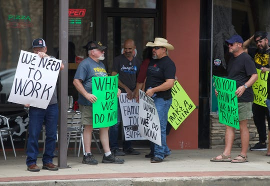 Demonstrators protest in downtown San Angelo on Saturday, June 27, 2020 against the governor's order to close bars again due to rising positive cases of the coronavirus.