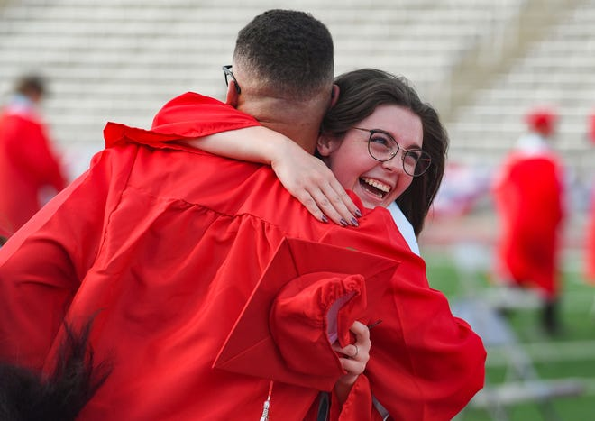 Students embrace each other as they celebrate the completion of Lincoln High School's commencement on Saturday, June 27, Howard Wood Field in Sioux Falls.