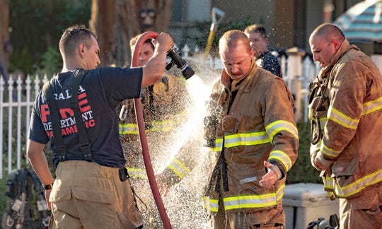 Visalia Fire Department rinses off equipment after battling a structure fire in the 1000 block of North Highland Street on Saturday, June 27, 2020. Three fire engines, two firetrucks, a battalion chief and an ambulance were dispatched just after 6 p.m. A neighbor saw the fire and notified the two people at home in time for them to evacuate safely. No injuries were reported. The fire started at the rear of the home and spread inside to the kitchen and the attic. The cause is under investigation.