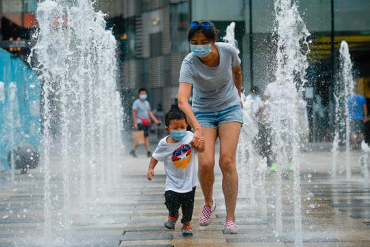 "A woman and a child wearing face masks walk past a row of fountains in a business district in Beijing on June 28, 2020. Chinese health officials said on June 28 that Anxin county about 90 miles from Beijing, will be ""fully enclosed and controlled"", the same strict measures imposed at the height of the pandemic in the city of Wuhan earlier this year."