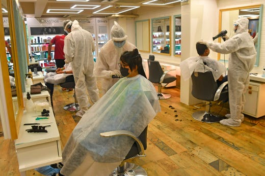 Staff at Shiva's Signature hair salon wearing Personal Protective Equipment suits and face shields attend customers after personal grooming services were allowed to resume following relaxation of lockdown norms amidst COVID-19 coronavirus pandemic, in Mumbai on June 28, 2020. India now has more than 500,000 confirmed coronavirus cases, according to government figures released on June 27 that showed a record daily leap of 18,500 new infections.