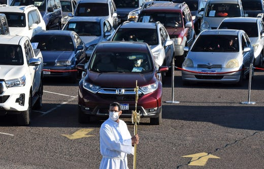 Faithful attend a drive-in mass at the Silvio Pettirossi International Airport parking in Luque, near the Paraguayan capital, on June 28, 2020, amid the COVID-19 novel coronavirus pandemic.  The pandemic has killed at least 498,779 people worldwide since it surfaced in China late last year, according to an AFP tally at 0930 GMT on Sunday based on official sources.