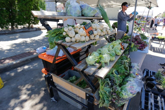 Vegetables sit on a stand at the Oshkosh Farmers Market on Saturday, June 27, 2020, in Oshkosh, Wis.
