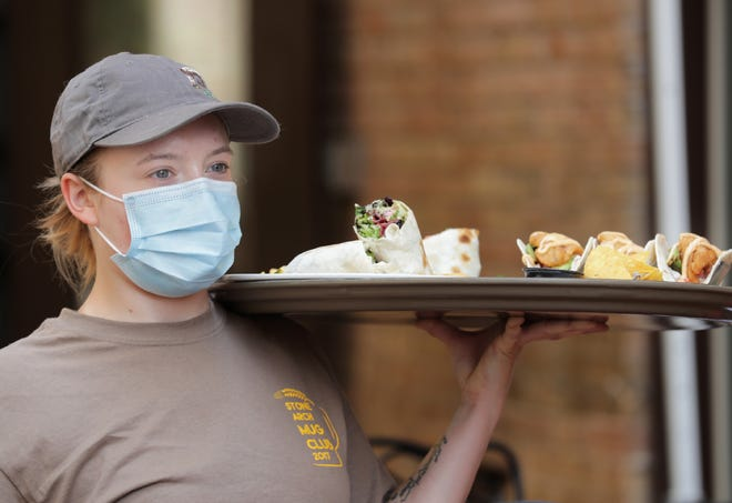Front of the house manager Lauren  Maggard serves food at Stone Arch Brewpub in Appleton. Workers are required to wear masks on the job.