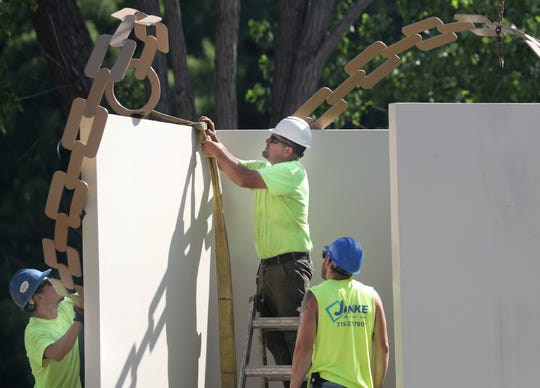 """Contractors move the heavy """"Metamorphosis"""" sculpture into place along the Fox River in Appleton."""
