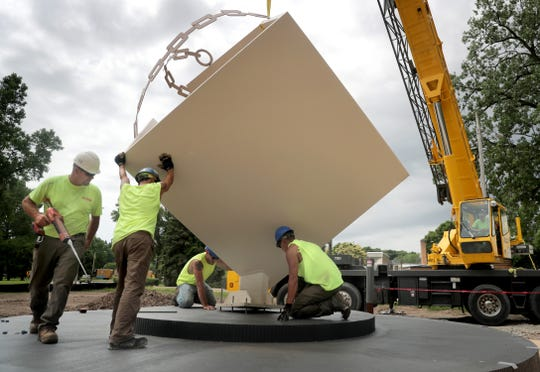 """Contractors mount the """"Metamorphosis"""" sculpture on its new base along the Fox River at the south end of the Lawe Street bridge in Appleton. The artwork anchored Houdini Plaza between 1985 and 2010."""
