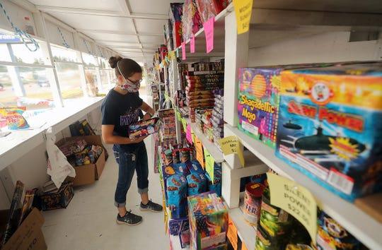 Emily Richardson stocks the shelves at Pyro Dave's Fireworks stand on Wheaton Way in Bremerton on Monday.