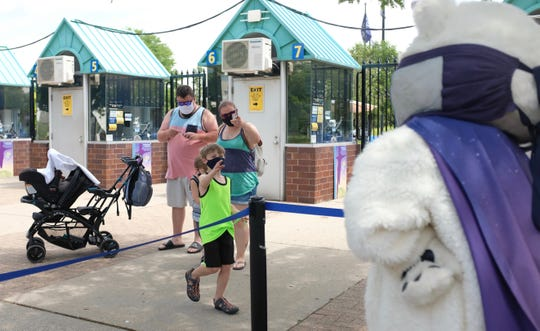Brandon Bielby, 8, of Warren, greets Nanook, a Detroit Zoo polar bear mascot, at the entrance of the zoo on Saturday, June 27th.