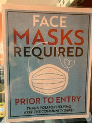 Mexican Fiesta restaurant in Dearborn Heights has a face mask sign posted on its door.