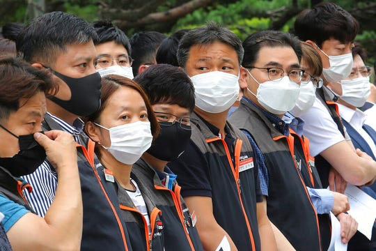 Financial union members wearing face masks to help protect against the spread of the new coronavirus attend a rally against government's financial policy in front of the Financial Supervisory Service in Seoul, Monday, June 29, 2020.
