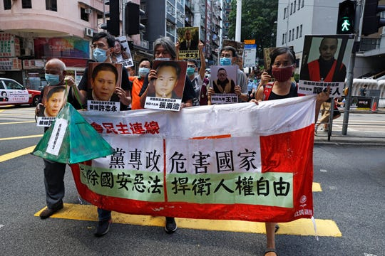 "Pro-democracy demonstrators hold up a banner and portraits of jailed Chinese civil rights activists, lawyers and legal activists as they march to the Chinese liaison office in Hong Kong, Thursday, June 25, 2020. The banner read ""One-party dictatorship harms the country, abolish the national security law and defend human rights and freedom in Hong Kong""."