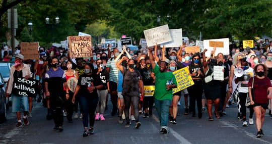 Hundreds of protesters march down Waterman Boulevard headed to St. Louis Mayor Lyda Krewson's home on Sunday in St. Louis.