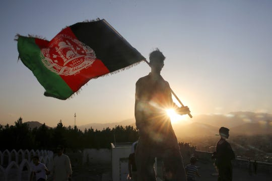 In this Aug. 19, 2019, file photo, a man waves an Afghan national flag during Independence Day celebrations in Kabul, Afghanistan.