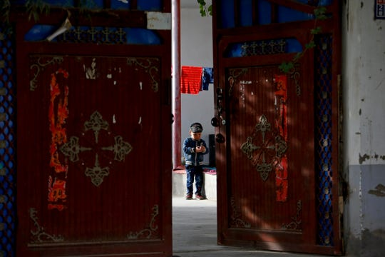 In this Sept. 20, 2018 photo, a Uighur child plays alone in the courtyard of a home at the Unity New Village in Hotan, in western China's Xinjiang region.