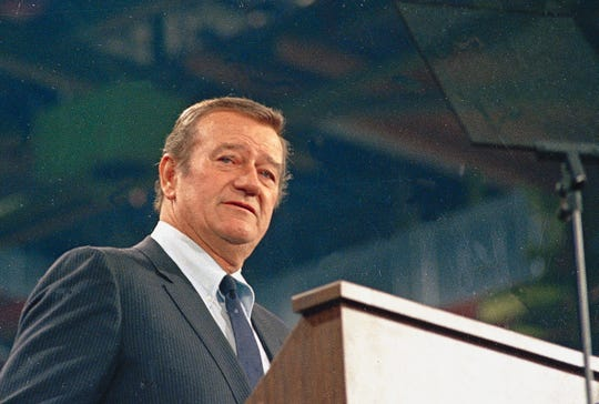 In this 1968 file photo, actor John Wayne looks on. In the latest move to change place names in light of U.S. racial history, leaders of Orange County's Democratic Party are pushing to drop film legend Wayn's name, statue and other likenesses from the county's airport because of his racist and bigoted comments.