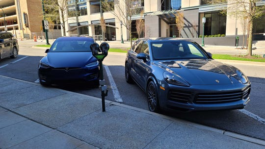 Meet the new boss. The plug-in, 2020 Porsche Cayenne E-Hybrid goes head-to-head with the all-electric Tesla Model X 9left). They take very different approaches to green luxury.