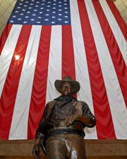 In this Sept. 11, 2011, file photo, a bronze statue of late actor John Wayne stands before a four-story high United States flag at John Wayne Orange County Airport in Santa Ana, Calif.