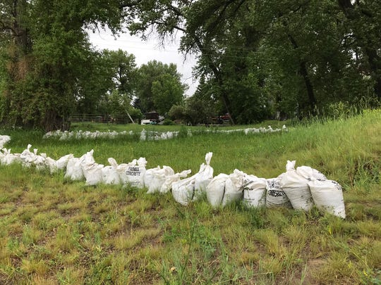 Sandbags are situated between the river and a home in Sun River.