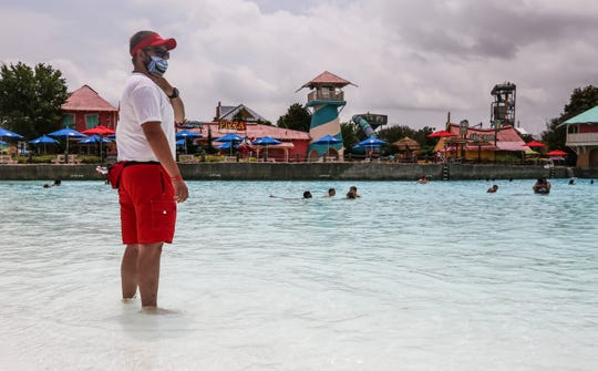Wearing a mask, lifeguard Dustin Tussey stands at watch on a humid, hot opening day at Hurricane Bay water park that is part of Kentucky Kingdom Monday. The park has set up physical distancing procedures and plenty of hand sanitizer. Face coverings for guests are encouraged by the park but not required.  June 29, 2020