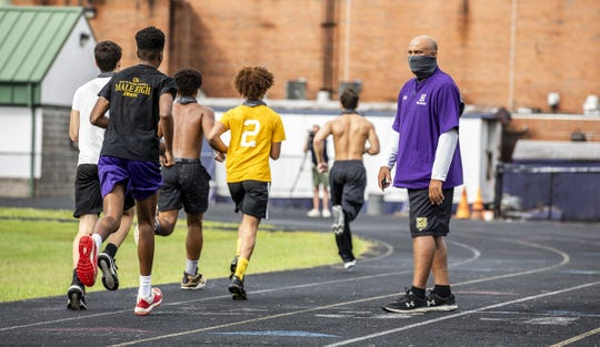 Male High School's DB Coach Moe Owens encouraged players as they ran by on the first day of conditioning for the 2020 football season. Monday, June 29, 2020.