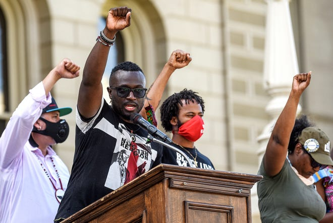 Pastor Sean Holland, of Epicenter of Worship church, holds up his fist with other speakers near the end of a statewide rally hosted by Black Lives Matter on Monday, June 29, 2020, at the Capitol in Lansing.
