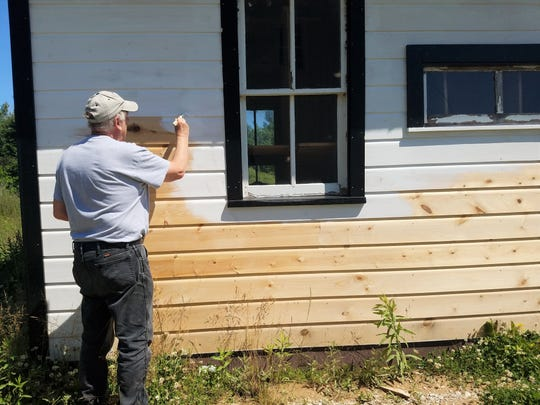 A volunteer works on the outside of the Meeme Poll House at Manitowoc County Historical Society's Pinecrest Historical Village in Manitowoc.