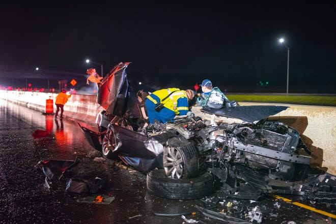 Rescue workers try to help a Sandusky man who was seriously injured when his car was hit by a semi on I-80 on Saturday night.