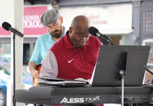 Song leader Alex Reese, foreground, leans in while playing the keyboard during the prayer rally held Sunday afternoon in downtown Marion.