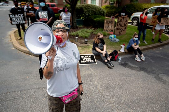 "L.J. Abraham leads protesters outside the offices of Financial Consulting Group in Germantown, Tenn., on Monday, June 29, 2020. The group was there in protest of one of the firm's partners, Lloyd Crawford, who was shown in a viral video confronting a protester carrying a ""Black Lives Matter"" sign on Saturday."