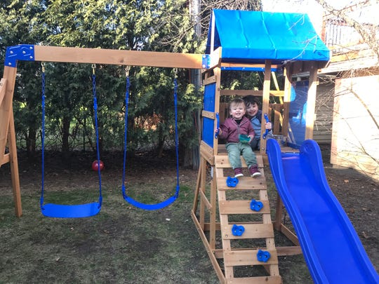 Finn and Fox Bruner enjoy their play set in their yard in Wauwatosa. Katie Bruner, their mother, bought a play-set in April after she and her husband could no longer take their sons to the park.