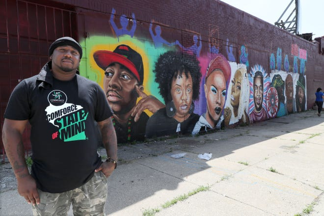 A mural depicting current black activists in Milwaukee was put on the side of a building at 1400 N. 14th St. The figure on the left on the mural is Vaun Mayes, who happened to be on site and agreed to stand for a photo in front of the artwork.