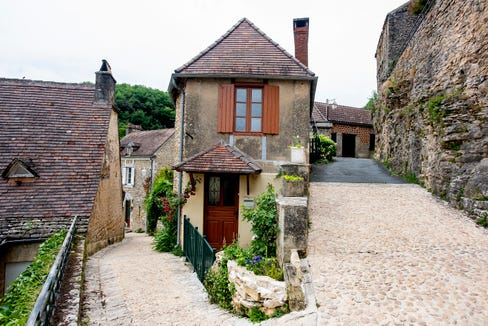 The village of La Roque Gageac rises steeply from the Dordogne River to a cliff face.