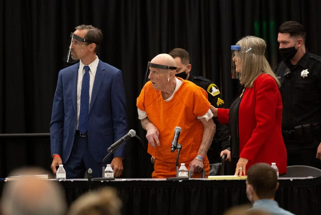 Joseph James DeAngelo, center, who is accused of being the Golden State Killer, is helped up by his attorney, Diane Howard, as Sacramento Superior Court Judge Michael Bowman enters the courtroom in Sacramento, Calif., on June 29. To accommodate the large number of people attending, the hearing was held at a ballroom at California State University to allow for social distancing.
