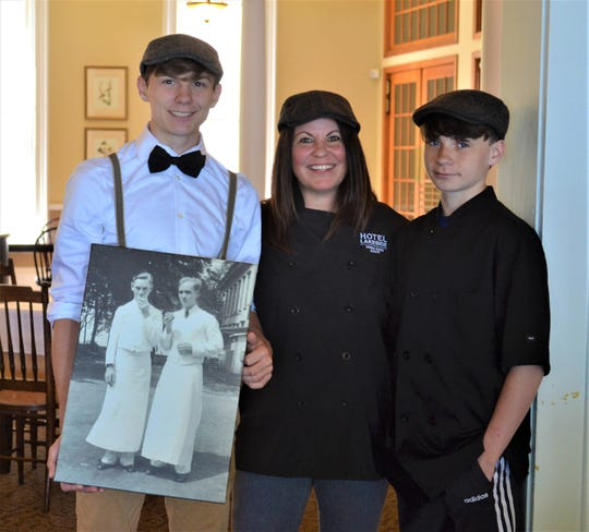 Chef Stacy Maple, shown here with her sons Christian Maple, left, and Noelton Maple, is bringing echanges to the Lakeside Hotel Dining Room this season. Christian, who will work as a server at the restaurant, is holding a photo of the dining room's first servers.