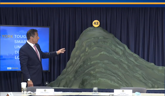 New York Gov. Andrew Cuomo unveils a giant mountain made of plastic foam at a news conference in Manhattan on June 29, 2020. The mountain is meant to visualize New York's COVID-19 battle.