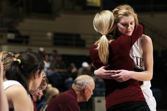 Bronte High School head coach Carol Moore hugs Kimber Lee as she walks off the court after fouling out in a regional quarterfinal playoff loss against Highland on Feb. 22, 2011.