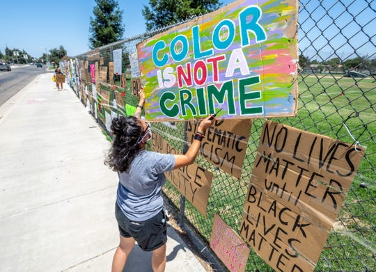 Ashley Machado and other Black Lives Matter supporters take down some signs along the El Diamante campus Monday afternoon amid concerns opponents were planning do so before Visalia Unified. They hope to find a new home for the signs.
