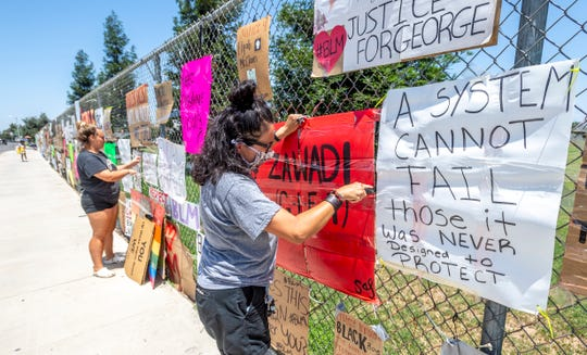 Black Lives Matter supporters Ashley Machado, right, Abigail Brown and Serena Salcido take down some signs along the El Diamante campus Monday afternoon amid concerns opponents were planning do so before Visalia Unified. They hope to find a new home for the signs.