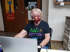 The masked library helper, Susan Manzke, volunteers at the Muehl Public Library, assisting with curbside delivery.