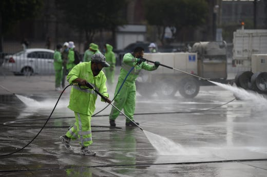 Workers disinfect and clean the Zocalo square in Mexico City on June 29, 2020 during the COVID-19 pandemic. Starting this week Mexico City is allowing the reopening of shops, street markets and athletic complexes but with limited capacity and hours. Hotels and restaurants in the capital will reopen at about 30% seating capacity.