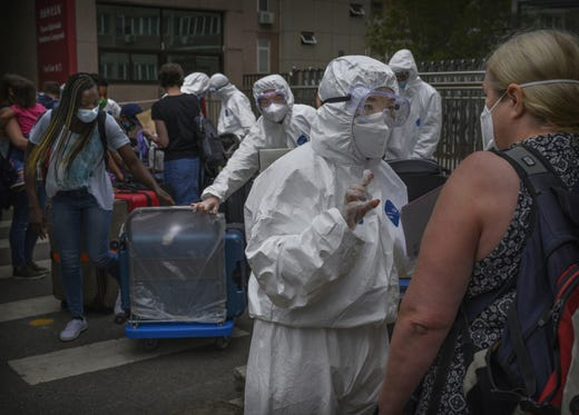 A Chinese epidemic control worker wears a protective suits as she talks to a foreign resident as she and others arrive to a residential compound as part of quarantine measures after arriving in China on June 29, 2020 in Beijing, China. In an effort to limit imported cases China closed its borders to non-citizens on March 28, 2020 allowing only those with special permission to enter the country. Those who do are required to complete 14 days of quarantine and week medical observation.