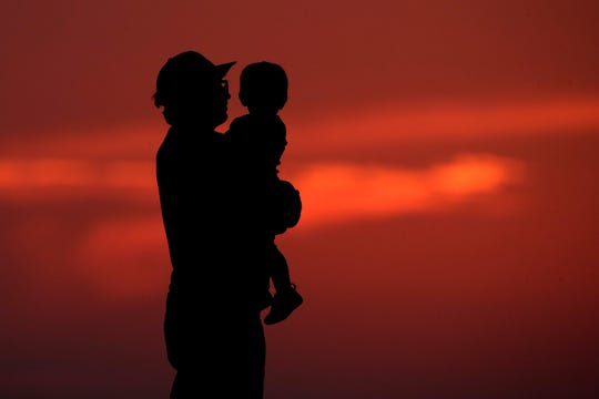 A man and his son are silhouetted against the sky as they watch the sunset from a park in Kansas City, Mo., Friday, June 26, 2020. Sunsets and sunrises were more vibrant than usual lately due to dust in the atmosphere from a Saharan dust cloud.