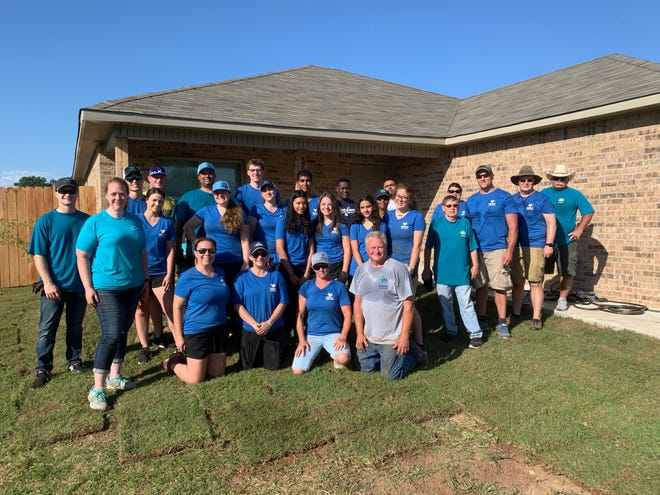 A group of volunteers from the Ardmore Valero Refinery lay sod at a Habitat for Humanity home.