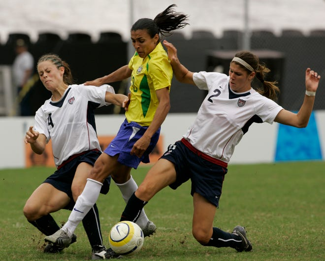 Brazil's Marta Silva, center, passes between Kaley Fountain, (4), and Brittany Taylor, (2), of the United States, during their women's soccer gold medal game at the Pan American Games in Rio de Janeiro, Thursday, July 26, 2007. Brazil won 5-0. (AP Photo/Ricardo Mazalan)