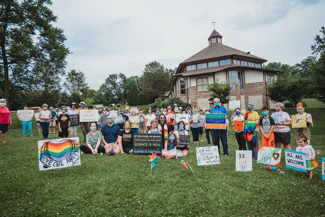 People rallied Monday at the Luther Church of the Resurrection in Anderson Township after a Pride display supporting the LGBT community was vandalized over the weekend.