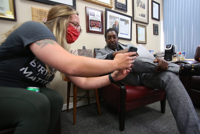 Lauren Hodson, case manager for the Detroit Recovery Project, meets with Andre Johnson, president/CEO of the Detroit Recovery Project on June 30.
