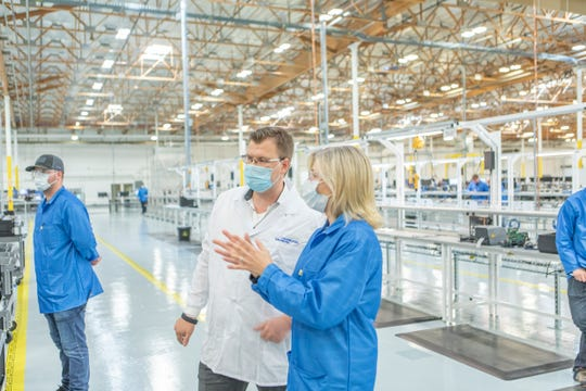 Jurij Kiesner, left, of Hamilton Medical AG in Switzerland talks with Ronda Uhl of General Motors as ventilator production begins in the background on May 1. The Swiss expert came over to inspect the assembly line and the ventilators after the project was completed.